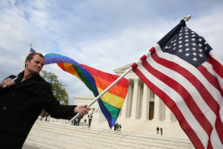 A support of marriage equality stands with a rainbow flag and a United States flag near protestors on the steps of the United States Supreme Court ahead of oral arguments in three landmark same-sex marriage cases. Plaintiffs in the Tanco vs. Haslam case, the lead case for same-sex marriage in Tennessee, meet with members of the media on the steps of the United States Supreme Court in Washington, DC on Monday, April 27, 2015.