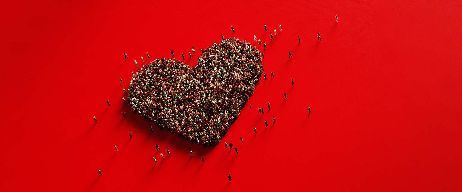 Human Crowd Forming A Big Heart Shape On Red Background: Love and Donation Concept