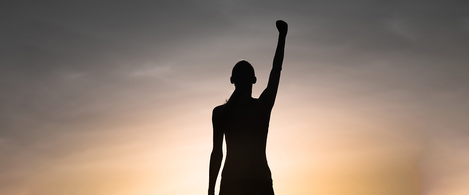 Strong, victorious and motivated young woman raising her fist up to the sunset sky.